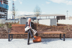 Middle-aged contemporary businessman sitting on a bench outdoor in the city reading newspaper talking smart phone - work, conversation, information concept