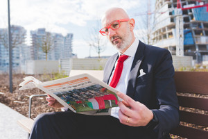 Middle-aged contemporary businessman sitting on a bench outdoor in the city reading newspaper - work, conversation, information concept