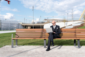 Midlle age caucasian businessman sitting on bench in the city using laptop - working, technology, business concept