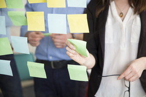 Midsection Of Businesswoman Sticking Note While Standing By Executive