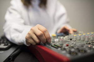 Midsection Of Radio Host's Hand Using Music Mixer In Studio