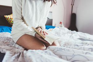 Midsection of young woman reading book lying on her bed - student, education, relaxing concept