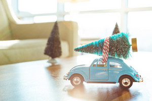 Miniature blue car carrying a Christmas tree on its roof