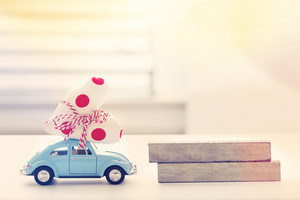 Miniature blue car carrying a polka dots heart cushion