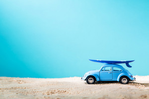 Miniature blue car with surfboard on a bright blue background