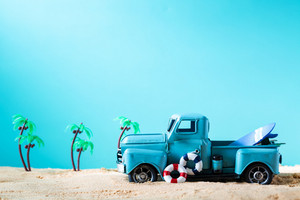 Miniature blue truck with surfboard and buoy on a bright blue background