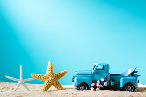 Miniature blue truck with surfboard and starfish on a bright blue background