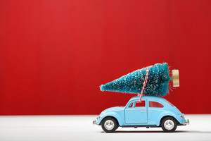 Miniature car carrying a Christmas tree on red colored wooden wall