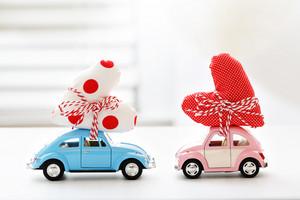 Miniature cars carrying a polka dots heart cushion