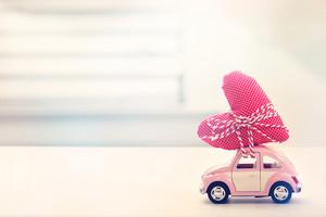 Miniature pink car carrying a heart cushion
