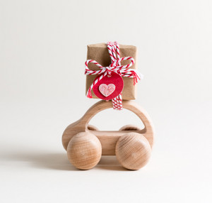 Miniature toy car carrying a small gift box