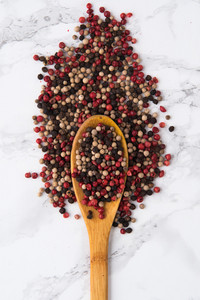 Mix of a pepper spice grains in a wooden spoon on a marble table