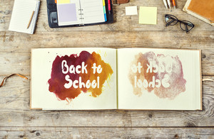 Mix of office supplies and Back to school sign on a wooden desk background. View from above.