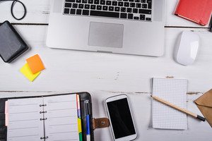 Mix of office supplies and gadgets on a white wooden table background. View from above.