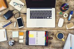Mix of office supplies and gadgets on a wooden desk background. View from above.