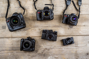 Mix of old cameras on wooden desk background.