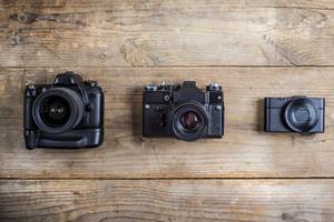 Mix of old cameras on wooden desk background.