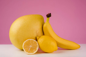 Mixed citrus fruit including lemon, pomelo and banana isolated on a pink background