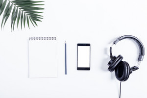 Mobile phone, black headphones, notebook, pencil and green leaves lie on a white table top view