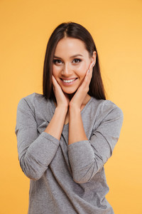 Model with hands on cheeks in studio. isolated orange background