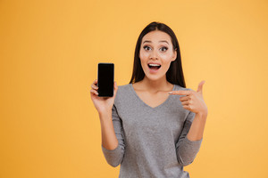 Model with phone in studio. looking at camera. isolated orange background.