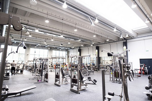 Modern gym with various exercise machines in it, people working out