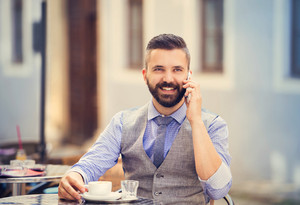 Modern hipster businessman drinking espresso coffee in the city cafe during lunch time and calling by mobile phone