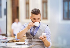 Modern hipster businessman drinking espresso coffee in the city cafe during lunch time and using mobile phone