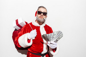 Modern man santa claus with gift sack smoking and holding money