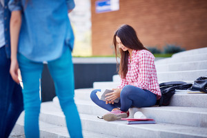 Modern teen girl in casualwear reading book outdoors