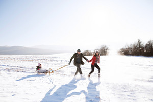 Mother and father pulling daughter on sledge, running. Beautiful family in sunny winter nature.