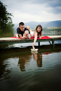 Mother and father with baby boy sitting on pier and playing with paper boat