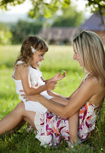 Mother and little daughter spending time togetger in summer garden.
