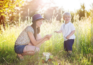 Mother and little son enjoying sunshine outside in nature