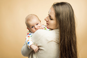 Mother holding a baby tenderly in her arms studio shot on beige background