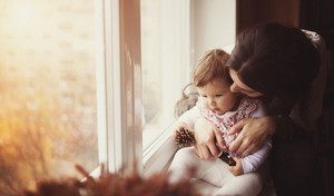 Mother with her baby daughter by the window