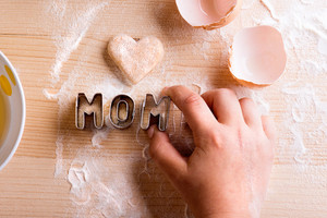 Mothers day composition. Baking cookies. Hands of unrecognizable girl holding cookie cutters. Pastry heart and egg shells laid on table. Studio shot on wooden background.