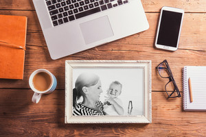 Mothers day composition. Black-and-white photo in picture frame. Office desk. Studio shot on wooden background.