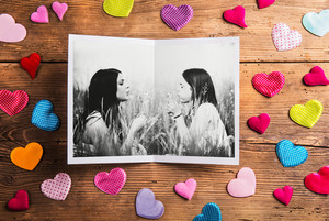Mothers day composition.  Black and white photo of mother with her daughter. Colorful fabric hearts. Studio shot on wooden background.