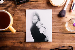 Mothers day composition. Black-and-white picture of mother holding her little baby, cup of coffee and various make up products. Studio shot on wooden background.