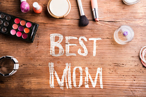 Mothers day composition. Chalk Best mom sign and various beauty products on table. Studio shot on wooden background. Flat lay.
