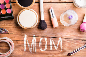 Mothers day composition. Chalk Mom sign and various beauty products on table. Studio shot on wooden background. Flat lay.