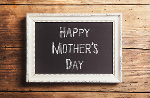 Mothers day composition. Chalk sign in picture frame. Studio shot on wooden background.