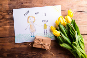 Mothers day composition. Childs drawing of her and her mother, bouquet of yellow tulips and little gift. Studio shot on wooden background.