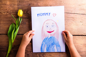 Mothers day composition. Hands of unrecognizable child holding a drawing of her mother and a yellow tulip. Studio shot on wooden background.