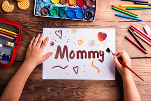 Mothers day composition. Hands of unrecognizable child painting picture for her mother. Studio shot on wooden background.