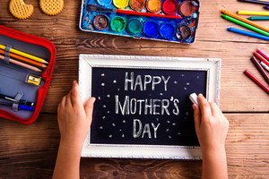 Mothers day composition. Hands of unrecognizable child writing with chalk on black board in white picture frame. Studio shot on wooden background.