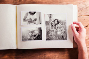 Mothers day composition. Hands of unrecognizable man holding a photo album, black-and-white pictures. Studio shot on wooden background.