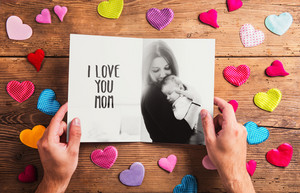 Mothers day composition. Hands of unrecognizable man holding black and white photo of mother with her baby daughter. Colorful fabric hearts. Studio shot on wooden background.