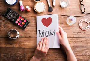 Mothers day composition. Hands of unrecognizable woman holding greeting card. Various beauty products. Studio shot on wooden background.